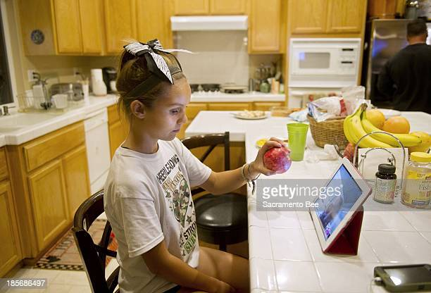 Olivia Torres holds up a pomegranate to show her mom she is eating healthy at the family home in Galt, California, October 10 while skyping with her...