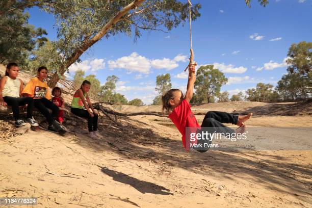 Olivia Whyman swings from a tree onto the dry bed of the Darling -Barka river on March 04, 2019 in Wilcannia, Australia. The Barkandji people -...