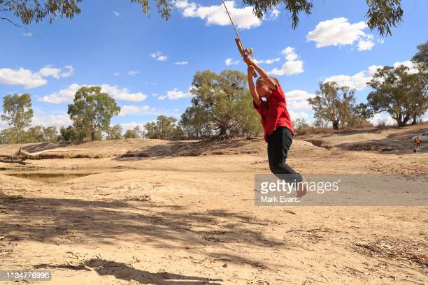 Olivia Whyman swings from a tree onto the dry bed of the Darling Barka river on March 04 2019 in Wilcannia Australia The Barkandji people meaning the...