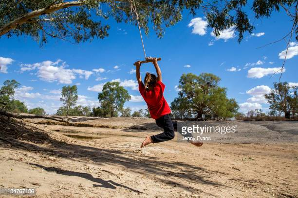 Olivia Whyman swings from a tree over the dry bed of the Darling -Barka river on March 04, 2019 in Wilcannia, Australia. The Barkandji people -...