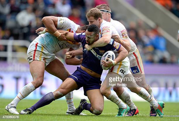 Olivier Elima Remi Casta and Scott Dureau of Catalans Dragons tackle Jodie Broughton of Huddersfield Giants during the Super League match between...