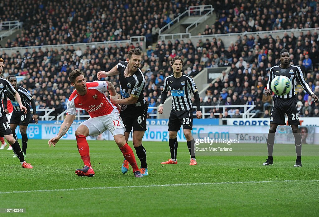 Olivier Giroud beats Newcastle defender Mike Williamson to score the 1st Arsenal goal during the Barclays Premier League match between Newcastle United and Arsenal at St James' Park on March 21, 2015 in Newcastle upon Tyne, England.