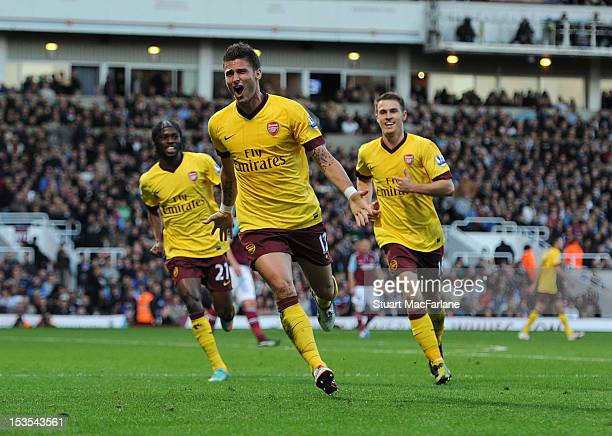 Olivier Giroud celebrares scoring for Arsenal with Gervinho and Aaron Ramsey during the Barclays Premier League match between West Ham United and...