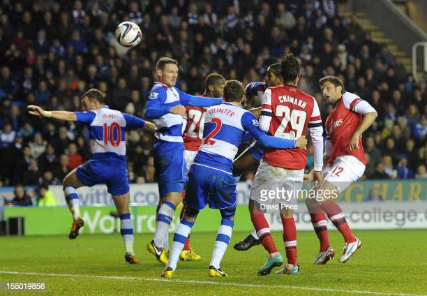 Olivier Giroud heads Arsenal's second goal past Sean Morrison of Reading during the Capital One Cup match between Arsenal and Reading at Madejski...
