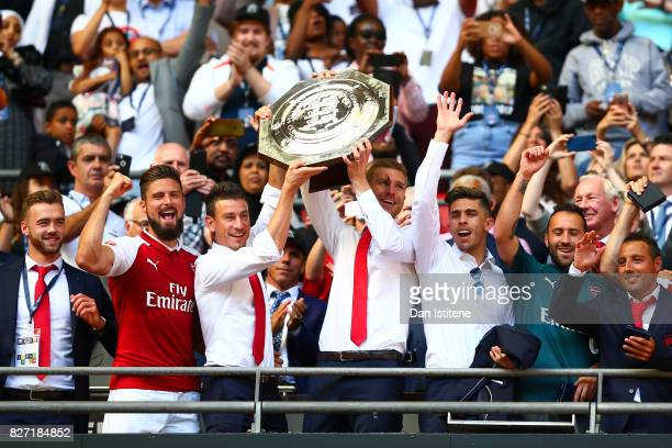 Olivier Giroud Laurent Koscielny Per Mertesacker and Gabriel Paulista of Arsenal celebrate with the FA Community Shield after victory in the FA...