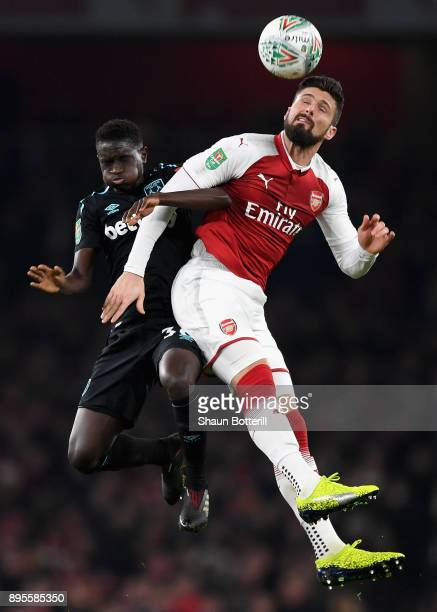 Olivier Giroud of Arsenal and Domingos Quina of West Ham United jump for the ball during the Carabao Cup QuarterFinal match between Arsenal and West...