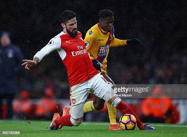 Olivier Giroud of Arsenal and Wilfried Zaha of Crystal Palace compete for the ball during the Premier League match between Arsenal and Crystal Palace...