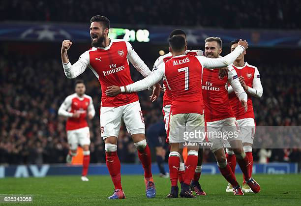 Olivier Giroud of Arsenal celebrates his sides second goal with his Arsenal team mates after Marco Verratti of PSG scored a own goal during the UEFA...