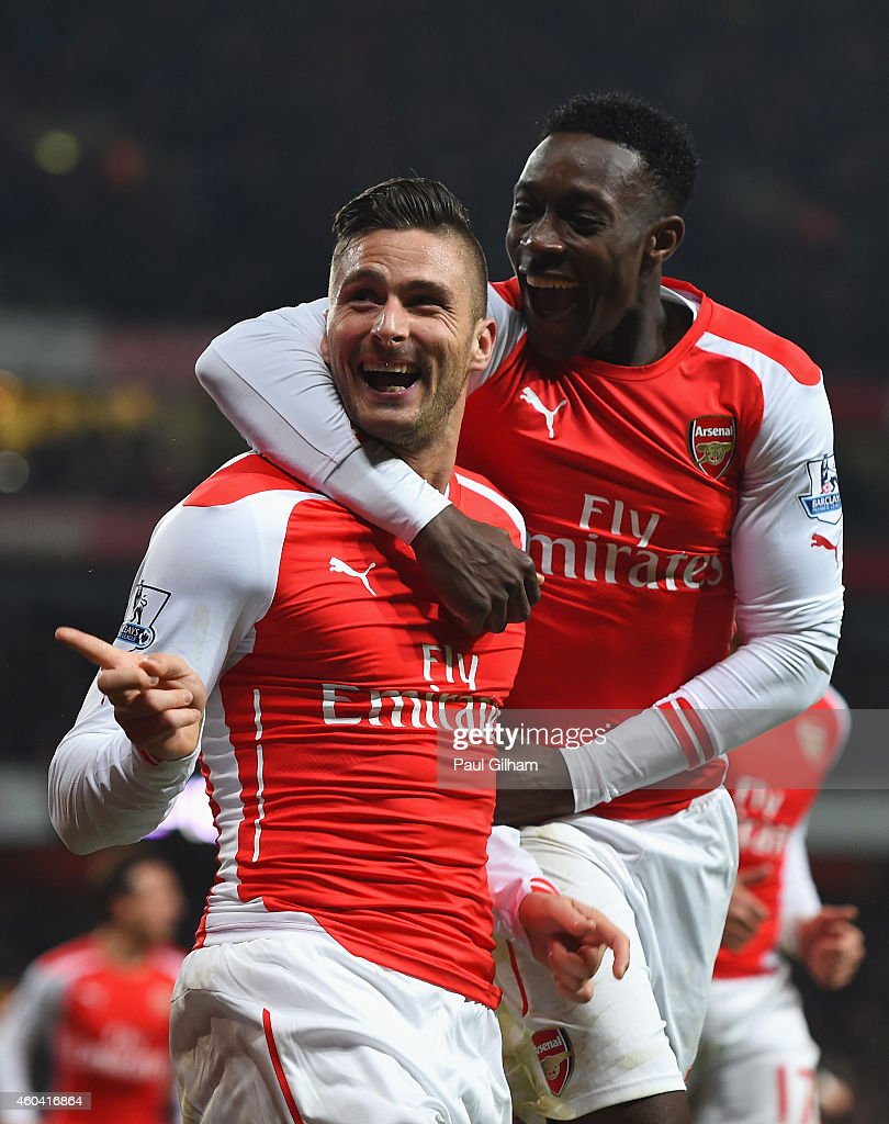 Olivier Giroud of Arsenal celebrates scoring his team's third goal with Danny Welbeck during the Barclays Premier League match between Arsenal and Newcastle United at Emirates Stadium on December 13, 2014 in London, England.