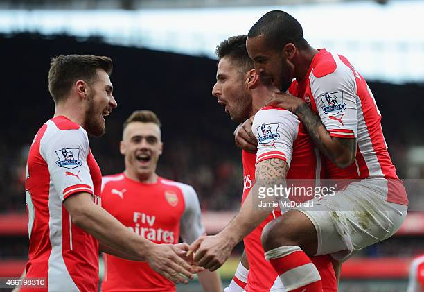 Olivier Giroud of Arsenal celebrates scoring the opening goal with Theo Walcott and Aaron Ramsey during the Barclays Premier League match between...