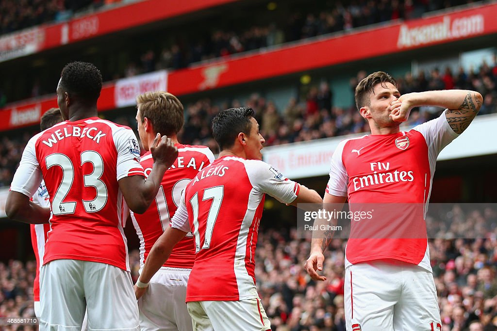Olivier Giroud of Arsenal (R) celebrates with team mates after scoring his team's fourth goal during the Barclays Premier League match between Arsenal and Liverpool at Emirates Stadium on April 4, 2015 in London, England.