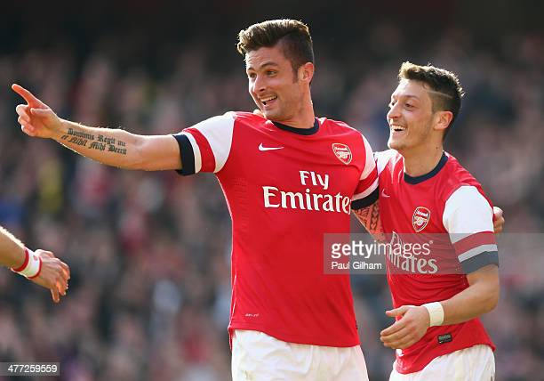 Olivier Giroud of Arsenal celebrates with teammate Mesut Oezil after scoring his team's fourth goal during the FA Cup QuarterFinal match between...