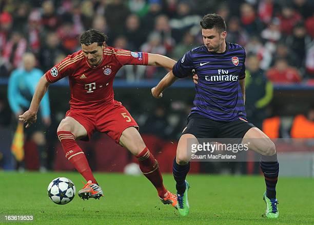 Olivier Giroud of Arsenal challenges Bayern Munich defender Daniel Van Buyten during the UEFA Champions League Round of 16 second leg match between...