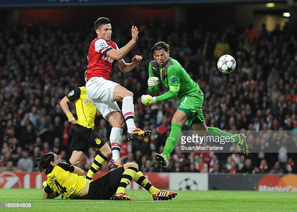 Olivier Giroud of Arsenal challenges goalkeeper Roman Weidenfeller of Dortmund on his was to scoring for Arsenal during the UEFA Champions League...