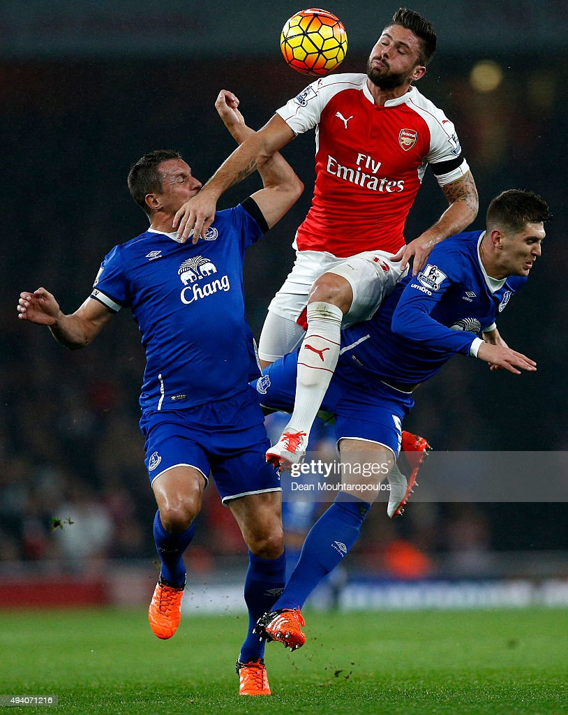 Olivier Giroud (C) of Arsenal competes for the ball against Phil Jagielka (L) and John Stones (R) of Everton during the Barclays Premier League match between Arsenal and Everton at Emirates Stadium on October 24, 2015 in London, England.