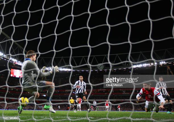 Olivier Giroud of Arsenal heads in their fifth goal past Tim Krul of Newcastle United during the Barclays Premier League match between Arsenal and...
