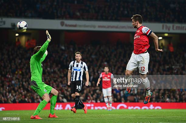 Olivier Giroud of Arsenal heads the ball past goalkeeper Tim Krul of Newcastle United to score their third goal during the Barclays Premier League...