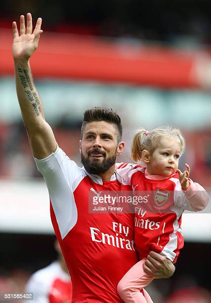 Olivier Giroud of Arsenal holding his child applauds supporters the Barclays Premier League match between Arsenal and Aston Villa at Emirates Stadium...