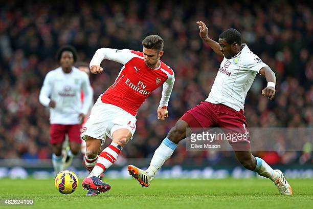 Olivier Giroud of Arsenal is challenged by Jores Okore of Aston Villa during the Barclays Premier League match between Arsenal and Aston Villa at the...