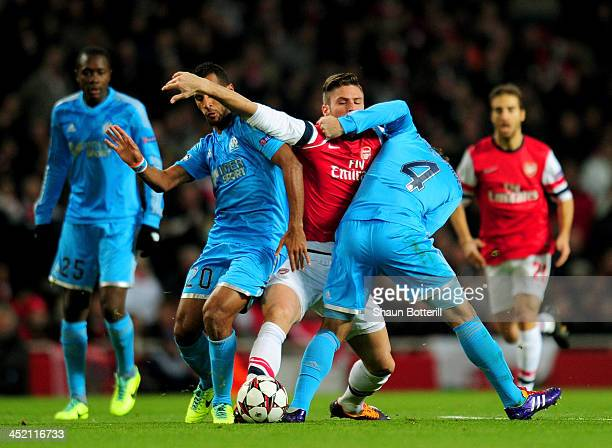 Olivier Giroud of Arsenal is closed down by Alaixys Romao and Lucas Mendes of Marseille during the UEFA Champions League Group F match between...