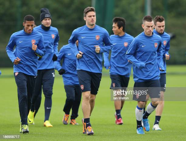 Olivier Giroud of Arsenal leads team-mates during a training session at London Colney on November 5, 2013 in St Albans, England.