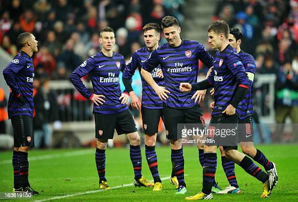 Olivier Giroud of Arsenal looks dejected with team mates during the UEFA Champions League Round of 16 second leg match between Bayern Muenchen and...