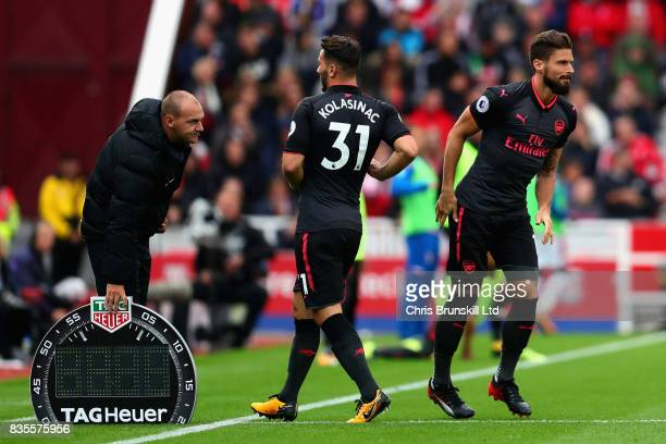Olivier Giroud of Arsenal replaces teammate Sead Kolasinac as a substitute during the Premier League match between Stoke City and Arsenal at Bet365...