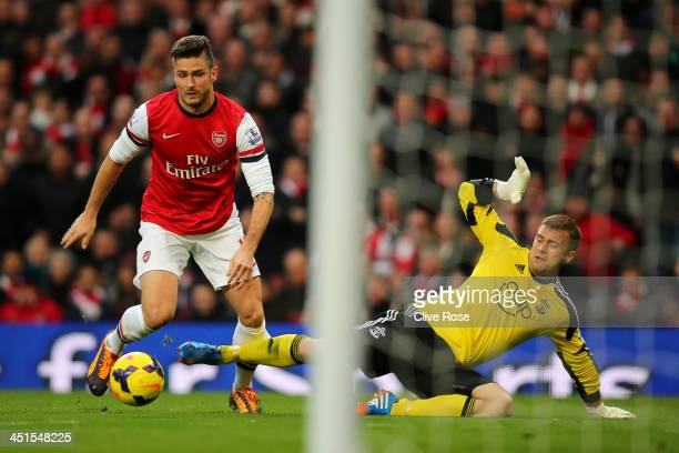 Olivier Giroud of Arsenal rounds goalkeeper Artur Boruc of Southampton before scoring the opening goal during the Barclays Premier League match...