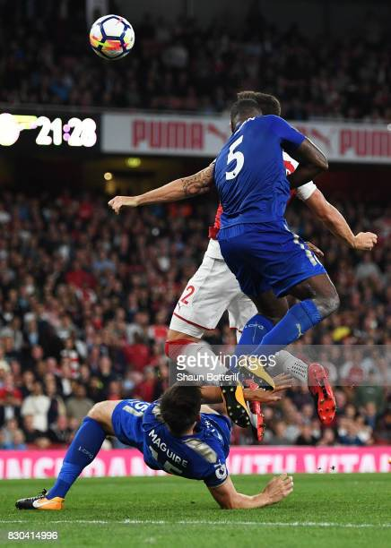 Olivier Giroud of Arsenal scores his team's fourth goal despite the attentions of Harry Maguire and Wes Morgan of Leicester City during the Premier...