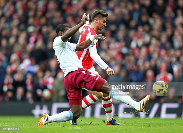 Olivier Giroud of Arsenal scores the opening goal despite the attention of Jores Okore of Aston Villa during the Barclays Premier League match...