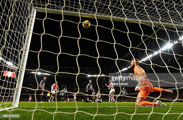 Olivier Giroud of Arsenal scores the opening goal past Jak Alnwick of Newcastle United during the Barclays Premier League match between Arsenal and...