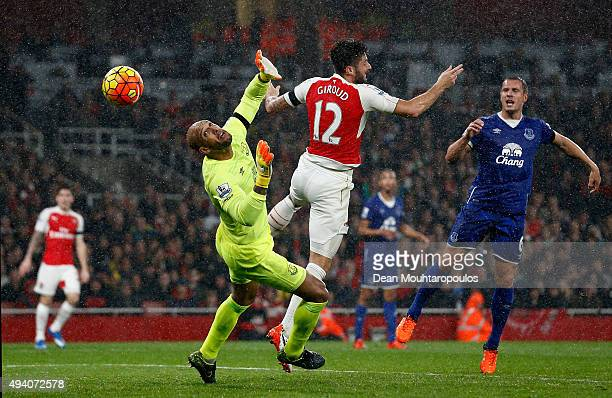 Olivier Giroud of Arsenal scores the opening goal past Tim Howard of Everton during the Barclays Premier League match between Arsenal and Everton at...