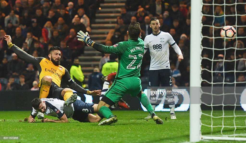 Olivier Giroud of Arsenal (L) shoots past Chris Maxwell of Preston North End to score their second goal during the Emirates FA Cup Third Round match between Preston North End and Arsenal at Deepdale on January 7, 2017 in Preston, England.