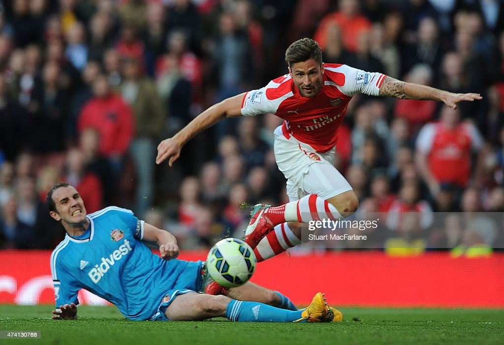 Olivier Giroud of Arsenal tackled by John O'Shea of Sunderland during the Barclays Premier League match between Arsenal and Sunderland at Emirates Stadium on May 20, 2015 in London, England.