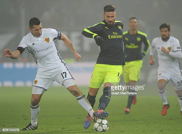 Olivier Giroud of Arsenal takes on Marek Suchy of Basel during the UEFA Champions League match between FC Basel and Arsenal at St JakobPark on...
