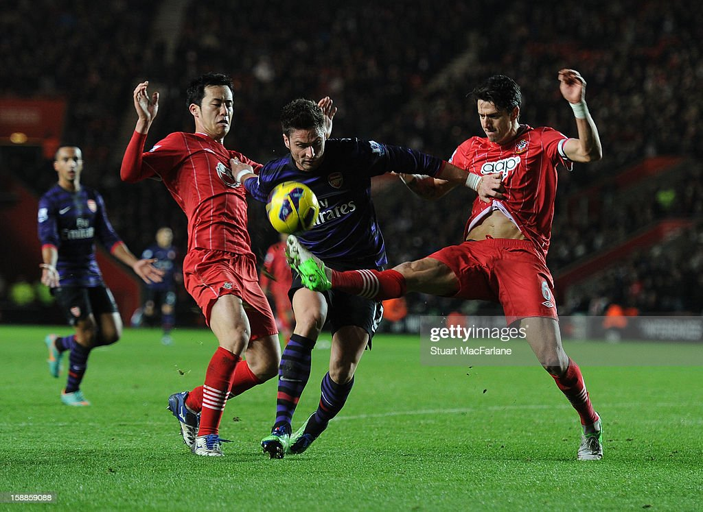 Olivier Giroud of Arsenal takes on Maya Yoshida (L) and Jose Fonte (R) of Southampton during the Barclays Premier League match between Southampton and Arsenal at St Mary's Stadium on January 01, 2013 in Southampton, England.