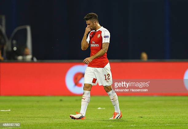 Olivier Giroud of Arsenal walks off after being shown the red card by referee Ovidiu Hategan during the UEFA Champions League Group F match between...