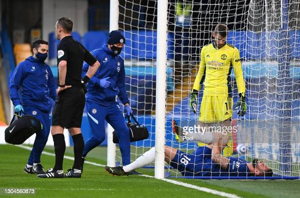 Olivier Giroud of Chelsea goes down injured and receives medical treatment as David De Gea of Manchester United looks on during the Premier League...