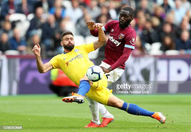 Olivier Giroud of Chelsea stretches for the ball under pressure from Arthur Masuaku of West Ham United during the Premier League match between West...
