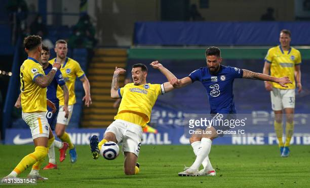 Olivier Giroud of Chelsea takes a shot under pressure from Lewis Dunk of Brighton & Hove Albion during the Premier League match between Chelsea and...