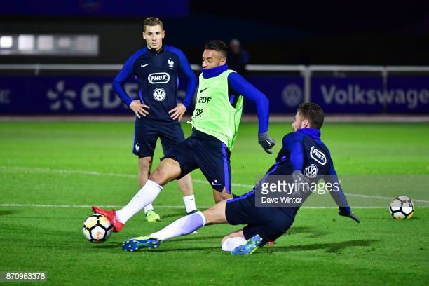 Olivier Giroud of France and Corentin Tolisso of France challenge for the ball as Lucas Digne of France looks on during the training session at the...