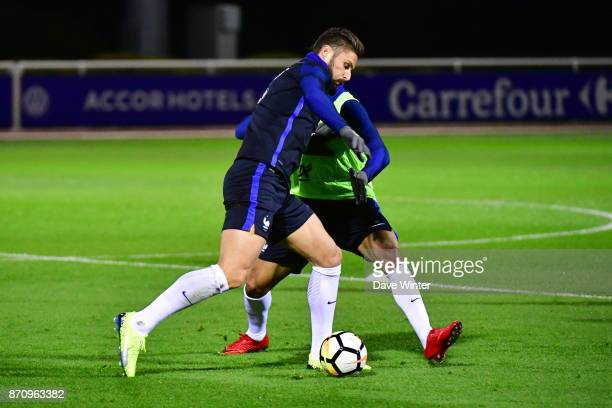 Olivier Giroud of France and Corentin Tolisso of France challenge for the ball during the training session at the Centre National de Football in...