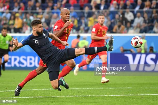 Olivier Giroud of France attempts a stop under pressure from Vincent Kompany of Belgium during the 2018 FIFA World Cup Russia Semi Final match...