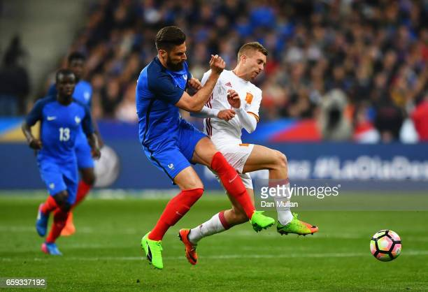 Olivier Giroud of France challenges Gerard Deulofeu of Spain during the International Friendly match between France and Spain at Stade de France on...