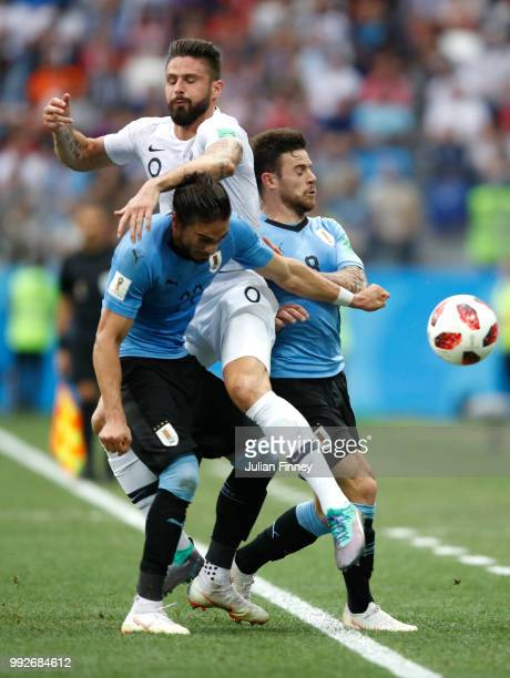 Olivier Giroud of France clashes with Martin Caceres and Nahitan Nandez of Uruguay during the 2018 FIFA World Cup Russia Quarter Final match between...