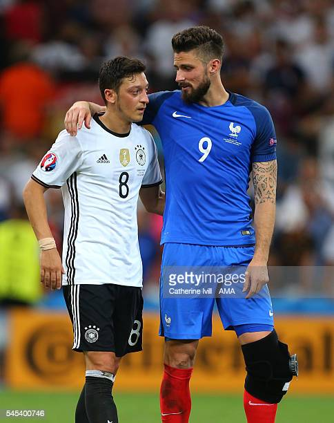 Olivier Giroud of France consoles a dejected Mesut Ozil of Germany after the UEFA Euro 2016 semi final match between Germany and France at Stade...