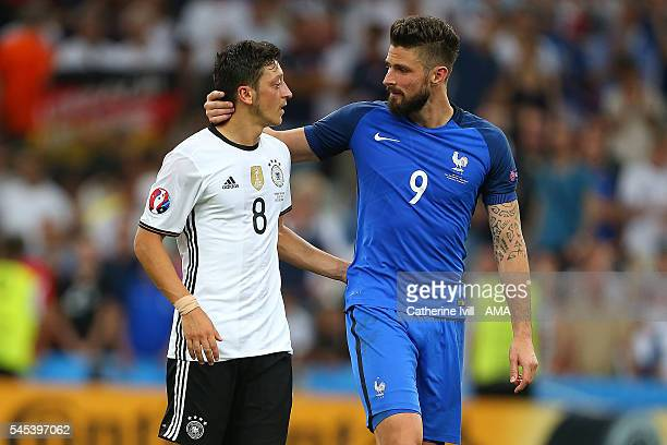 Olivier Giroud of France consoles Mesut Ozil of Germany at the end of the UEFA Euro 2016 Semi Final match between Germany and France at Stade...