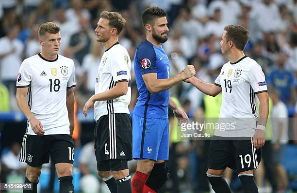 Olivier Giroud of France greets Mario Goetze of Germany while Toni Kroos and Benedikt Hoewedes of Germany look on following the UEFA Euro 2016...