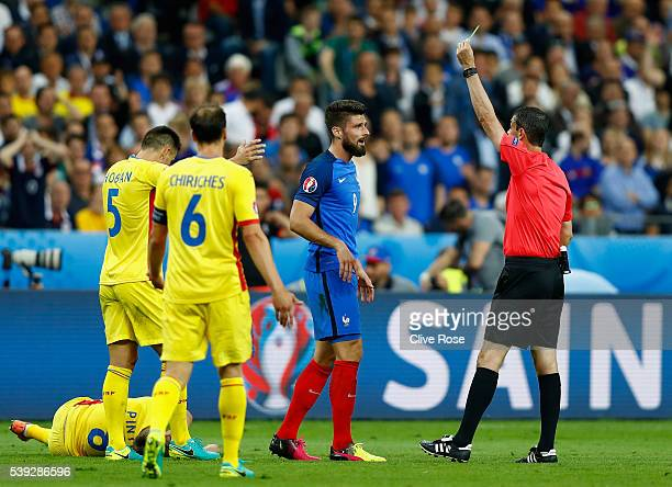 Olivier Giroud of France is shown a yellow card by referee Viktor Kassai during the UEFA Euro 2016 Group A match between France and Romania at Stade...