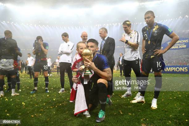 Olivier Giroud of France kisses the World Cup trophy with daughter Jade following the 2018 FIFA World Cup Final between France and Croatia at...